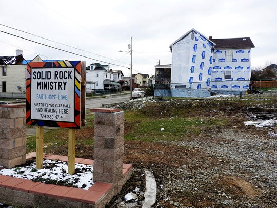 "In this March 2018 photo, a sign for Solid Rock Ministry is displayed near homes damaged by last month's tornado on Millview Street in Uniontown, Pa. Elmer ""Buzz"" Hall, pastor of Solid Rock Ministry sees the blue tarps on some houses in the surrounding neighborhood as a temporary fix and said he has been working to connect tornado-impacted residents with furniture and appliances."