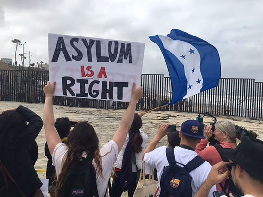 Central American migrants and supporters of the migrant caravan hold up signs from the U.S. side of the border looking south into Mexico on Sunday, April 29, 2018.