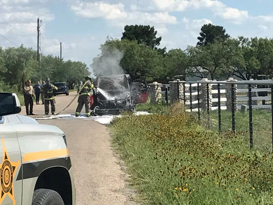 Firefighters douse a vehicle fire on Ratliff Road Thursday,