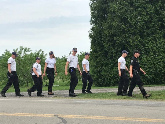 A group of searchers heads back to the command post on Joy Road in Sodus, part of the effort to find the missing 14-month old Owen Hidalgo-Calderon missing since May 16.