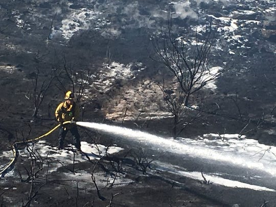 Firefighters battled a brush fire Monday afternoon