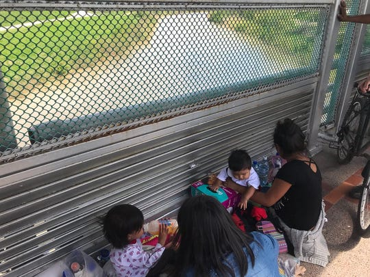 Two women seeking asylum on June 27, 2018, wait on the Mexico side of the border near Brownsville, Texas.