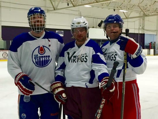 Trooper Berke Bates (right) and his brother Craig (middle) pause while playing ice hockey. Trooper Bates was killed in a helicopter crash near Charlottesville, Va. in the wake of violent protests on Saturday, August 12.