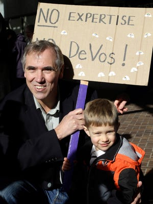 Sen. Jeff Merkley, D-Ore., left, poses with Asher Kockler and his sign for a family member during a rally in Portland, Ore., Friday, Jan. 27, 2017. Several hundred supporters gathered with Oregon congressional leaders in protest against Education Secretary nominee Betsy DeVos. (AP Photo/Don Ryan)