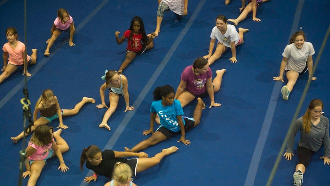 Campers and counselors for Aerial Antics, a summer camp designed to teach kids gymnastics, dance, and circus aerial practices, rehearse for their August 2015 performance on at Leisure Square in Vero Beach.