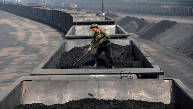 A worker levels the coal on a freight train in Taiyuan in northern China's Shanxi province. Coal has been the dominant fuel for power generation for a century because it is cheap, plentiful, and easy to ship and store. But it emits a host of pollution-forming gases and soot particles, and double the greenhouse gas emissions of its closest fossil fuel competitor, natural gas.