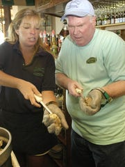 "In this file photo, Beachcomber reporter John Purnell gets a quick lesson on shucking oysters from Lori Kelley during ""Do My Job"" as a raw bartender at Harrison's Harborwatch in Ocean City."