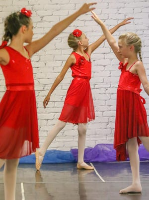 """Raegan Jones, 11, Zoey Walton, 11, and Adelynn Bettenbrock 11, perform their dance routine to the song """"Just Like Fire"""" during Vivette's Dance Studio's recital on Sunday at The Temple."""