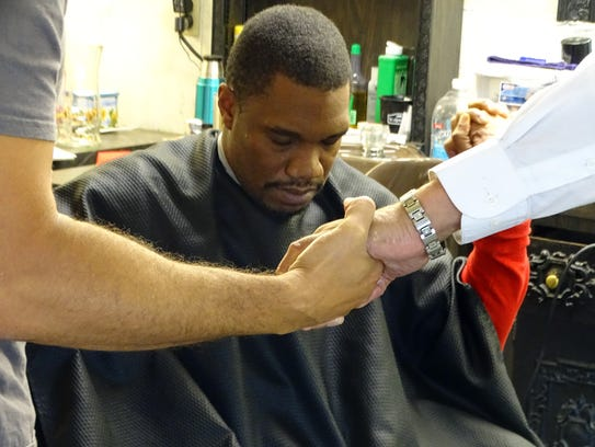 Antonio Staunton bows his head while sitting in a barber