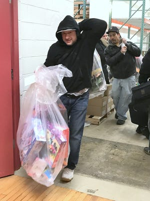 Volunteers leave Arctic League headquarters Christmas morning laden with gift bags for needy families.