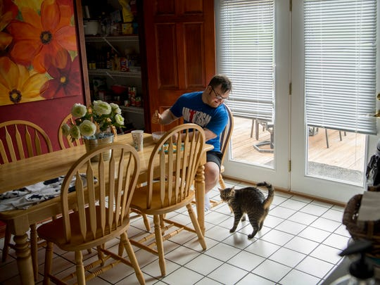 """With his cat, Spidey, his only company, Collin sits down for a meal he cooked consisting of oatmeal, egg whites with a little cheese and hot sauce in May of 2018. His other cat, Willow, was napping upstairs. Collin is still watching his diet closely so he can make his next bodybuilding """"cut"""" a little less of a strain."""
