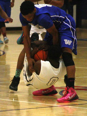 Redford Thurston's Teven Gary forces a jump ball while being lifted off the floor by Walled Lake Western's Daryl Porter.