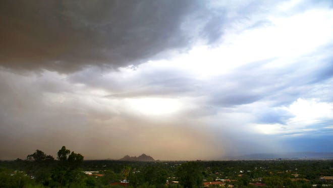 A monsoon storm moves over the Papago Buttes in Phoenix on Tuesday, August 11, 2015.