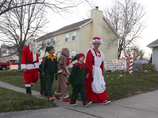 Brooke and Andy McHose of Ankeny, along with their children, dress up as Santa and Mrs. Claus, elves and a gingerbread man to get into the holiday spirit in their Ankeny neighborhood. This year the tradition of Gingerbread Lane is back, after a bad ice storm damaged property and decorations years ago.