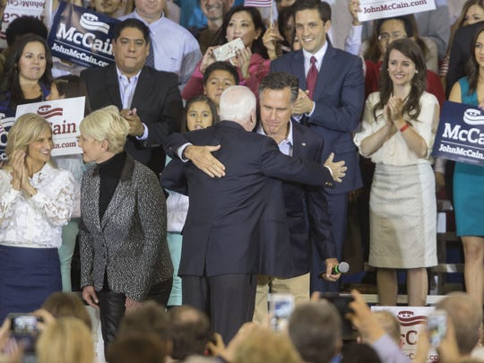 Sen. John McCain hugs Mitt Romney during a rally for McCain's re-election campaign at Dobson High School in Mesa on Dec. 12, 2015.