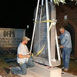 """Workers place the Ten Commandments monument in its new home at the Oklahoma Council of Public Affairs, just down the street from the state Capitol, in Oklahoma City, early Tuesday, Oct. 6, 2015.  The monument was removed from the state Capitol late Monday after the Oklahoma Supreme Court's decision in June that the display violates a state constitutional prohibition on the use of public property to support """"any sect, church, denomination or system of religion."""" (AP Photo/Sue Ogrocki)"""