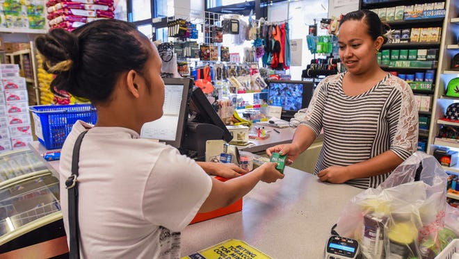 Cashier Melody Mori, right, hands customer Kimie Louis, 20, a pack of cigarettes purchased aat the Maxi Mart II store in Tamuning on Tuesday, Feb 21, 2017.