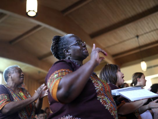 Naomi Dzikunu sings with the choir during service on