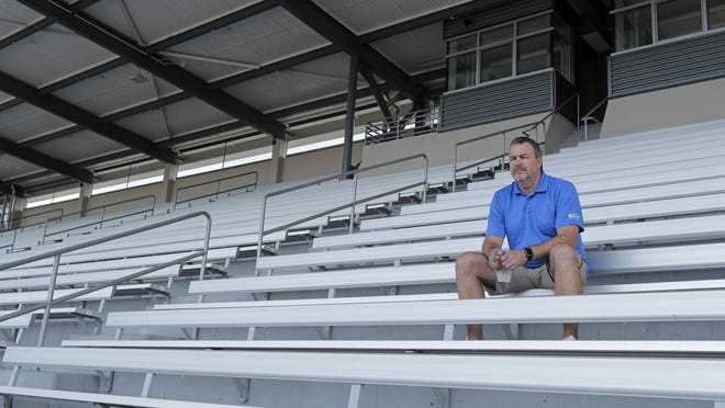 Mick Hoffman, executive director of the Washington Interscholastic Activities Association, poses for a photo on July 16, sitting in the empty stands of the Renton School District's Renton Memorial Stadium, which is used for high school football, soccer and track events in Renton, Wash.