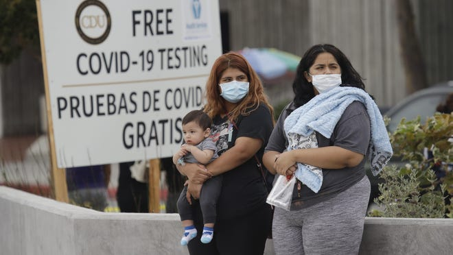 Two women and a child wait to take a Coronavirus test at a mobile testing site at the Charles Drew University of Medicine and Science on Wednesday in Los Angeles.