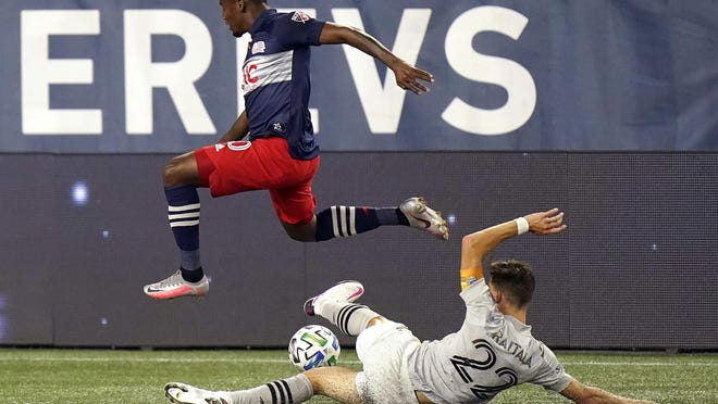 The New England Revolution's Cristian Penilla, left, leaps over the Montreal Impact's Jukka Raitala while pursuing the ball during the second half of their match Wednesday at Gillette Stadium.