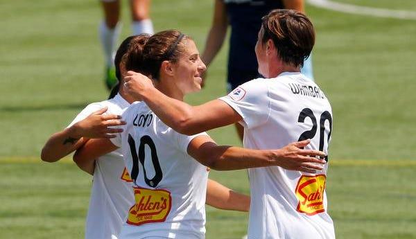 Flash's Carli Lloyd, center, hugs Samantha Kerr, left, and Abby Wambach during a July game at Sahlen's Stadium.