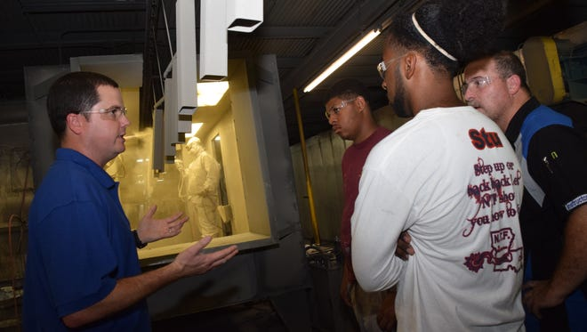 Justin Borland, (left), Baker Manufacturing manufacturing manager, talks to CLTCC auto collision students Kevin Sarpy (second from left) and Jamal Mills (far right) and CLTCC auto collision instructor Shannon Parker (right, center) about the parts that are powder coated at the Pineville plant. Baker Manufacturing makes office furniture.  Students from CLTCC and the Youth Challenge Program were touring the plant as part of Manufacturing Day.