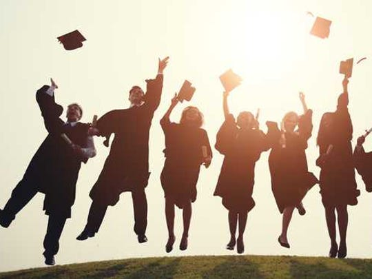 A group of grads jumping up and throwing their hats with backlighting.