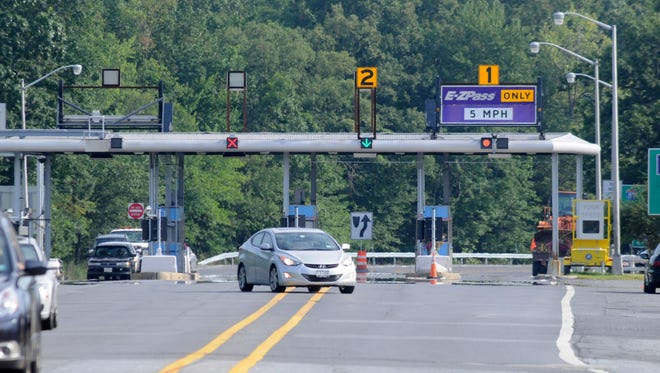 Traffic funnels through a tollbooth on the New York State Thruway.
