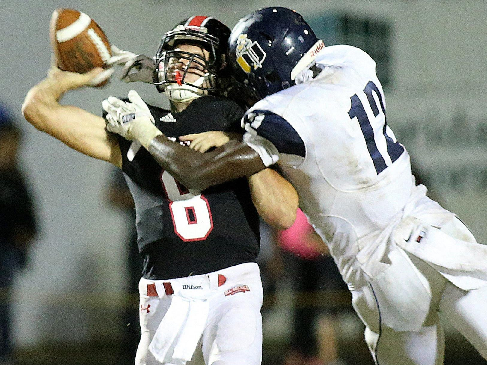 NFC backup quarterback Joey Giaritelli gets nailed by University Christian's Antonio Simmons in the first half of a playoff game two years ago.