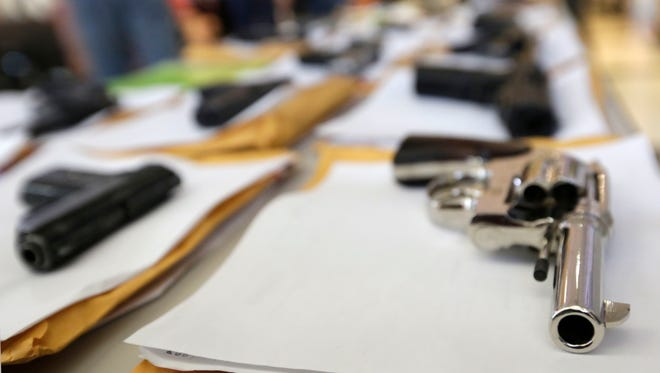 In this July 7, 2014, photo, Chicago police display some of the thousands of illegal firearms they have confiscated.