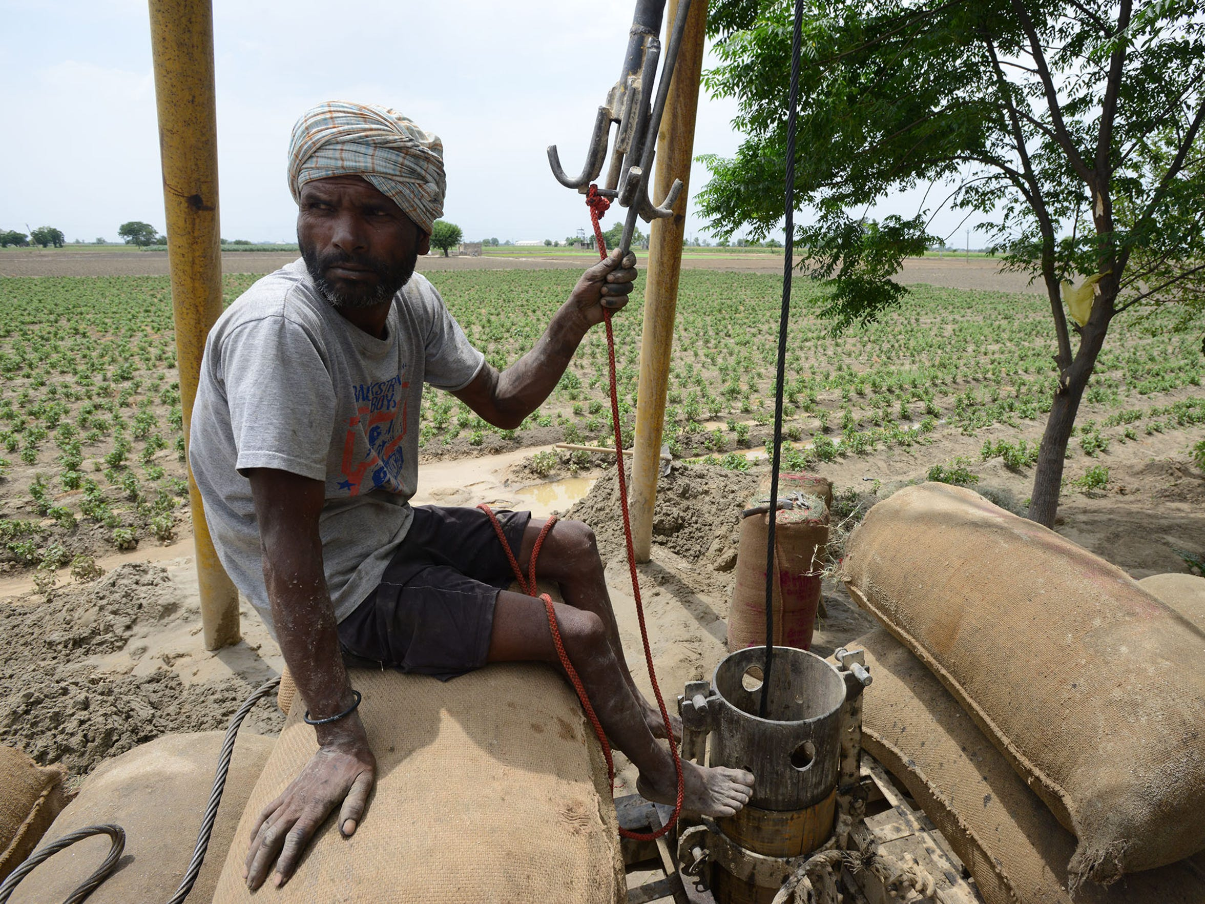 Santar Pal pauses from while digging a new tube well in the northern Indian state of Punjab. Groundwater levels have been falling as water is heavily pumped for farms. Many new wells are being drilled across the countryside.