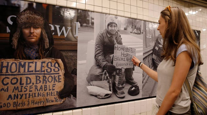 "Amanda Lachman of New York looks at portraits of the homeless by photographer Andres Serrano displayed on the walls of the West 4th Street subway station in New York. Lachman said, ""They really caught my eye. They're really powerful images that show people what life can really be like, and that these people need help."""