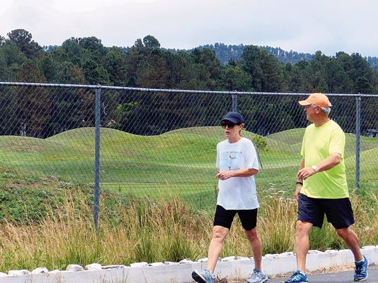 Despite rain clouds overhead, a couple enjoys a brisk walk on The Links trail in Ruidoso.