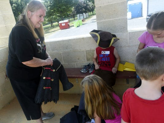 Donna Prettyman, left, helps children dress in pirate costumes for a pirate-themed party Saturday, Aug. 16, celebrating her retirement after running a day care center for 47 years.