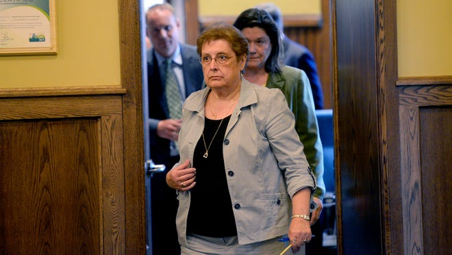 Board of Water & Light commissioners, including Sandra Zerkle, front, come out of a closed meeting after discussing a settlement agreement for fired former BWL general manager J. Peter Lark Tuesday. The board voted to accept the $650,000 settlement package for Lark.