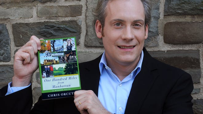 """Chris Orcutt of Millbrook, holds his book, """"One Hundred Miles from Manhattan."""""""