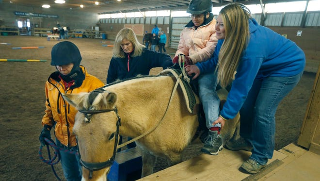 Instructor Sam Schaubroeck of Webster helps Tracie Kratzenberg of Webster get on Elvis, as volunteers Tammy Tingley of Penfield and Joan Harrington of Irondequoit wait during a session for riders with disabilities at Heritage Christian Stables in Webster. The therapeutic riding program is part of Heritage Christian Services.