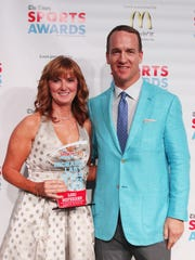 Peyton Manning poses with Richard Lary Coach of the Year Award winner Lori McFerren of North DeSoto at The Times Sports Awards at the Shreveport Convention Center on Monday.