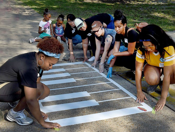 Civic volunteers prepare to paint a design onto a crosswalk