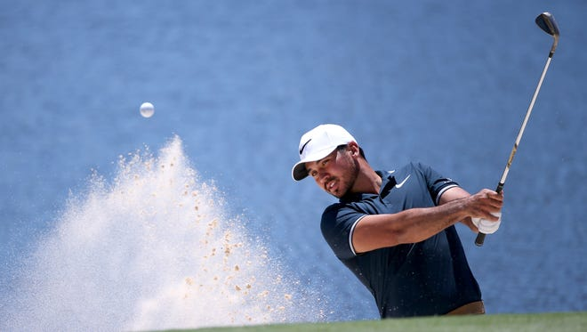 Jason Day hits a shot from the sand on the fourth green during the third round of the Australian Open on Saturday.