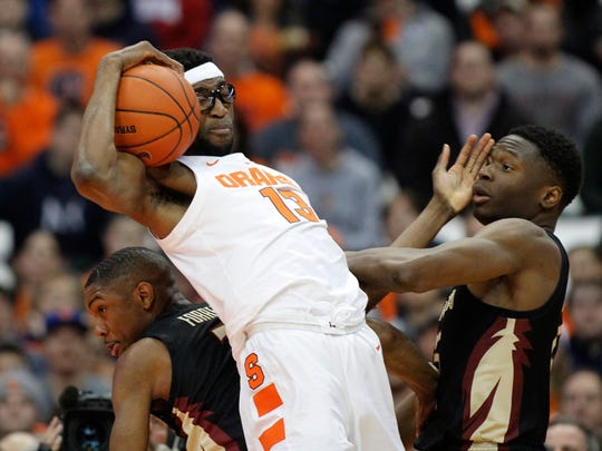 Syracuse's Paschal Chukwu, center, grabs a rebound from Florida State's Trent Forrest, left, and Mfiondu Kabengele, right, during the first half of an NCAA college basketball game in Syracuse, N.Y., Tuesday, Feb. 5, 2019. (AP Photo/Nick Lisi)