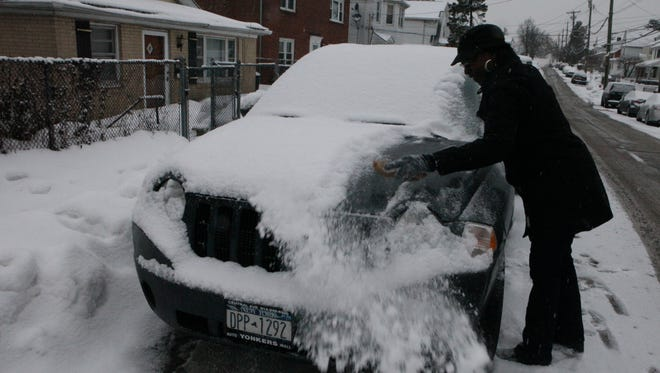 Princess Mayard brushes off the light powdery snow from her car on Rossiter Avenue in Yonkers after the early morning snowfall, Feb. 17, 2015.