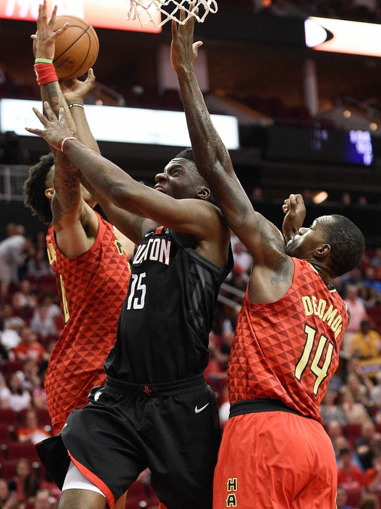 Houston Rockets center Clint Capela (15) drives to the basket between Atlanta Hawks guard Damion Lee, left, and center Dewayne Dedmon (14) during the first half of an NBA basketball game, Sunday, March 25, 2018, in Houston. (AP Photo/Eric Christian Smith)