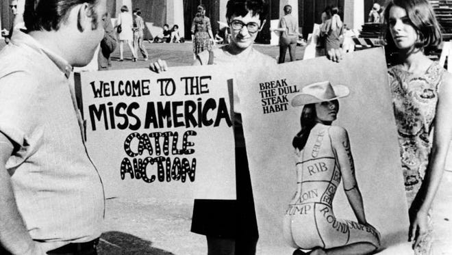 Members of the National Women's Liberation Party hold protest signs in front of Convention Hall where the Miss America Pageant will be held tonight in Atlantic City, N.J. on Sept. 7, 1968. The picketers, also seen behind, are protesting the annual pageant as degrading to women.