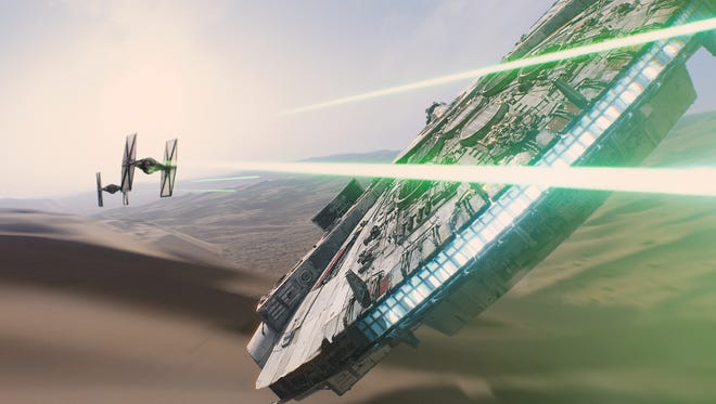 """The Millennium Falcon evades its pursuers in this scene from """"Star Wars: The Force Awakens,"""" which opens Dec. 18."""