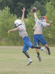 CrosLex's Austin Smith reaches for a pass as a teammate defends him during a practice.