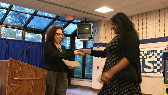 Nisha Gandhi, a teacher at Buzz Aldrin Middle School in Montclair, receives her Governor's Educator of the Year Awards from Montclair BOE President Jessica de Koninck during the May 3 BOE meeting.