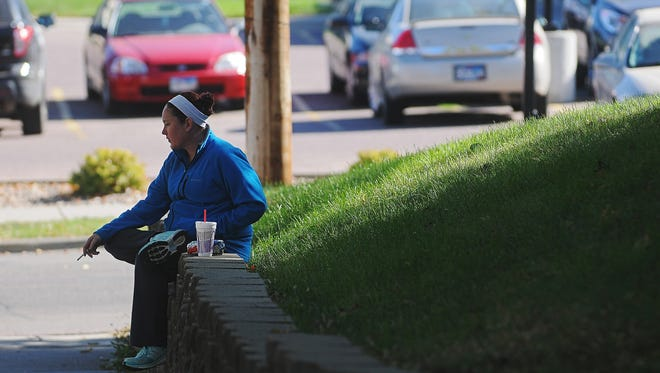 A woman smokes Wednesday, Oct. 14, 2015, near the corner of 7th Avenue and 20th Street across from the Avera McKennan Hospital & University Health Center in Sioux Falls.