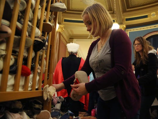 Abby Maas, of Pella adds a pair of baby shoes to the